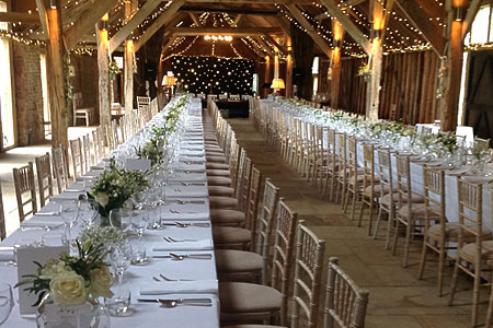 Party catering in a rustic barn with long tables laid for an event