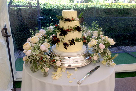 Wedding cake on a silver pedestal with flowers